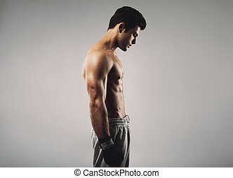 Fit young man wearing boxing gloves looking down - Side view...