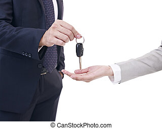 man handing car key to woman - close-up of males hand...
