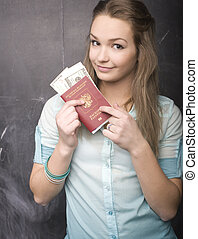 portrait of cute girl student with money and passport in...