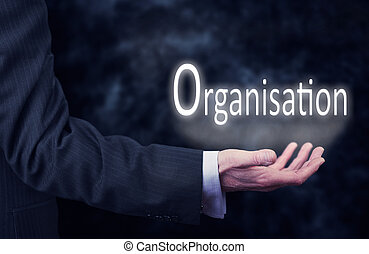 Organisation - A businessmans hand holding the word,...