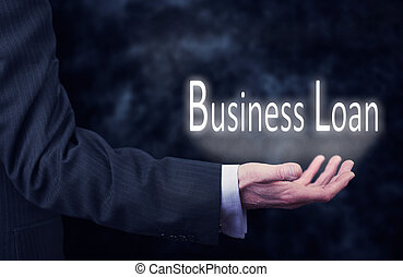 Business Loan - A businessmans hand holding the words,...