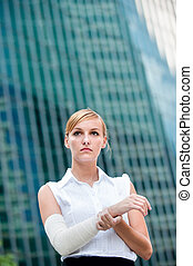 Businesswoman With Injured Arm - A young businesswoman holds...