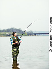Fisherman angling on the river - Mature fisherman angling on...