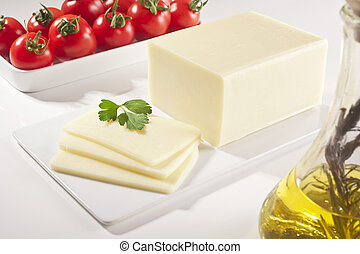 cheddar cheese - A block of cheddar cheese and cheese slices...
