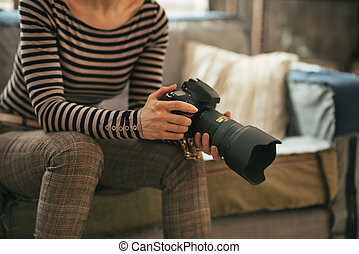 Closeup on young woman with modern dslr photo camera