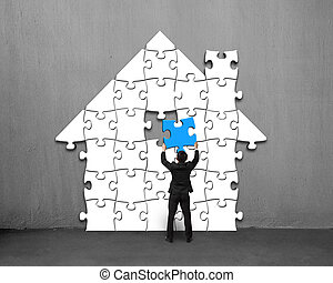 Assembling blue puzzles into house shape on concrete wall
