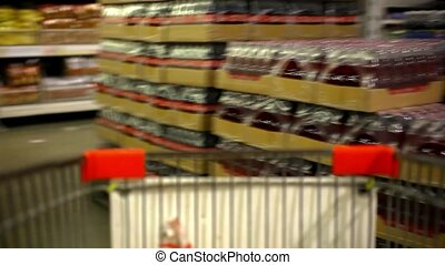 Customer shopping at supermarket with trolley. Video shift...