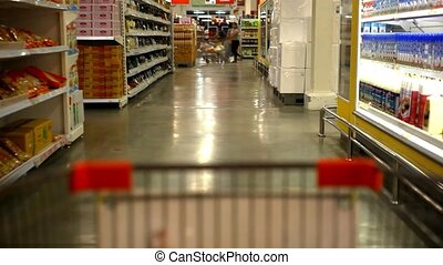 Customer shopping at supermarket with trolley Video shift...