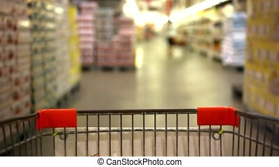 Customer shopping at supermarket with trolley and blurred...