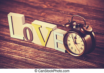 Alarm clock and word Love on wooden table