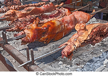 whole pigs roast - spit roasted a whole pigs cooked over hot...