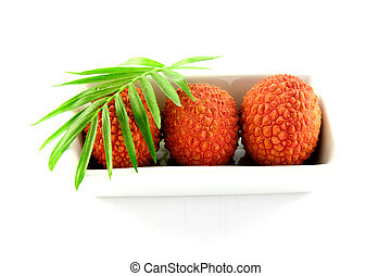 Three Lychee in a Dish - Three lychee and a green leaf in a...