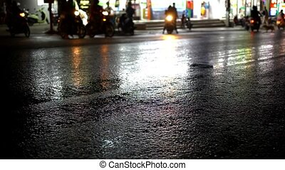 Cars and motorbikes driving on a wet road at night after...
