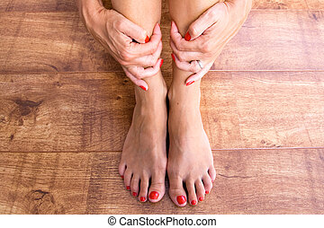 Feet and Hands - Feet placed on a wooden background with...