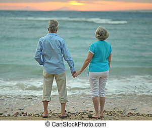 couple looking at sea - Senior couple looking at sea at...