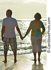 couple standing on beach - happy cute senior couple standing...