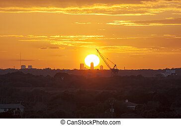 Carrying The Sun - The sunset view with a crane that looks...