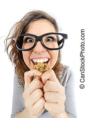 Funny geek girl eating a cookie isolated on a white...