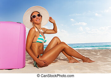 Happy woman with luggage on vacation