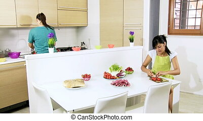 Two women preparing salad at home - Women having good time...