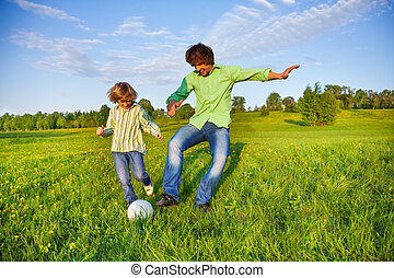 Father and boy playing football together in park - Father...