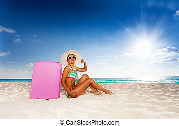 Happy woman with baggage on the beach