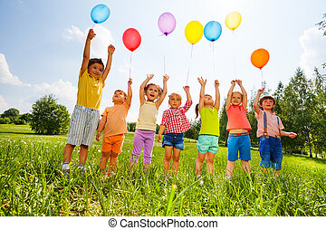Happy kids with balloons and arms up in the sky in green...