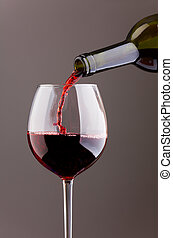 Wine pouring in glass on grey background - Wine pouring in...