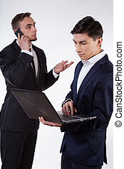 Two businessman during work with phone and computer