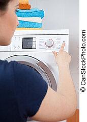 Housekeeper turning on washing machine - Housekeeper turning...