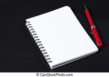 Diary and red pen on a granite table