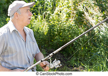 Elderly man fishing with a spinning reel
