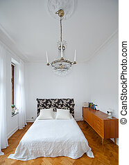 Bright bedroom with white walls and spartan chandelier