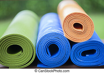 yoga mats - Colorful yoga mats set aside on the floor