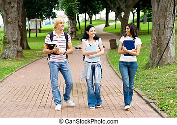 students walking and talking - students walking in the park...
