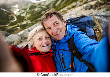Senior couple hiking - Senior tourist couple hiking and...