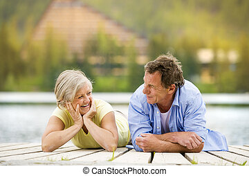 Senior couple on pier - Senior couple lying down and having...