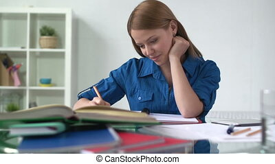 On the Beam - Close up of college girl doing homework while...