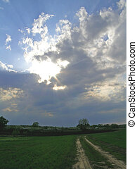 Sun rays breaking through the clouds before storm; rural...