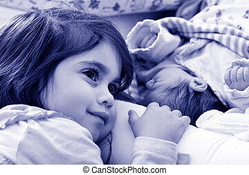 little girl and newborn sister - Happy little girl love and...