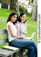 students with laptop on bench