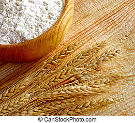 Wooden bowl full flour and wheat ears