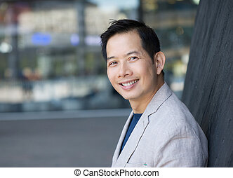 Trendy asian man smiling outdoors - Close up portrait of a...