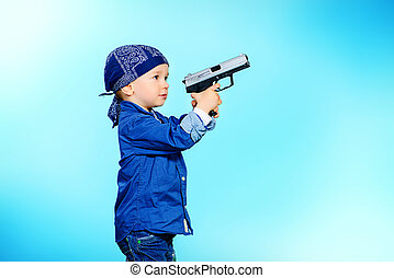 kid with gun - Cute 2 year old boy playing with a gun over...