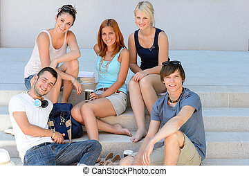 Students group sitting on school stairs smiling