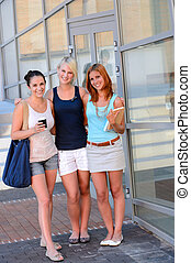 Three student girl friends outside college smiling summer...