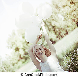 woman with balloons - happy young woman with white balloons...