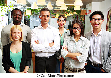 Group of a smiling businesspeople standing together in...