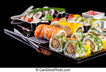 Delicious sushi pieces on black background - Various kind of...