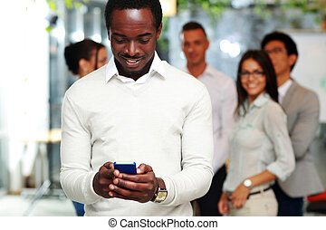 Happy businessman using smartphone in front of colleagues